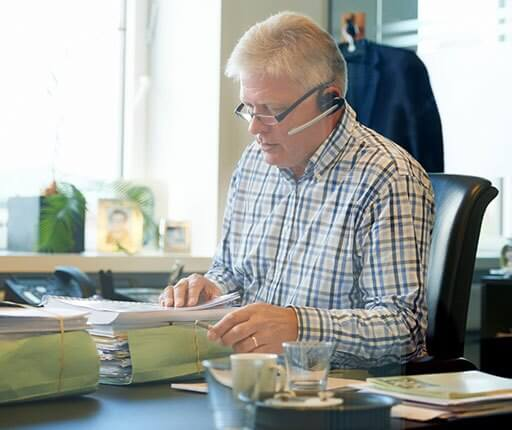 businessman on headset phone with files