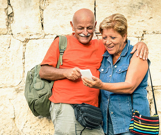Happy older couple traveling and using smartphone