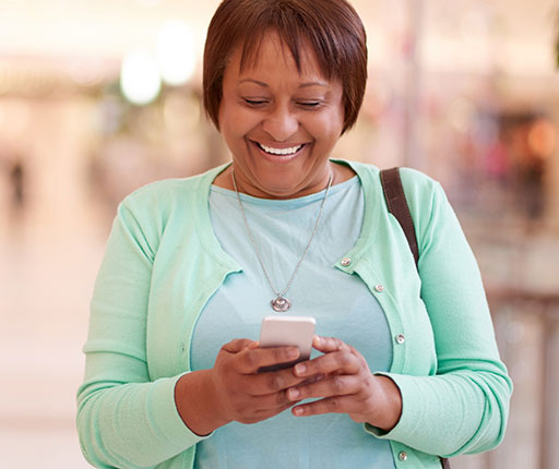 Smiling woman looking at mobile phone in mall