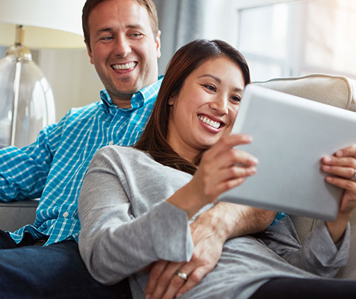 Happy couple on couch using tablet