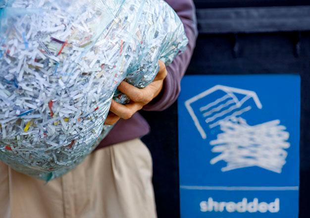 man holding bag of shredded paper