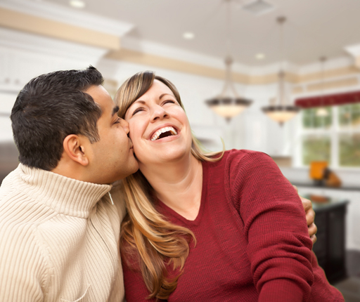 man kissing laughing wife at home