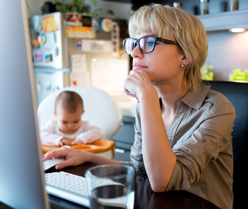 mother using computer in kitchen