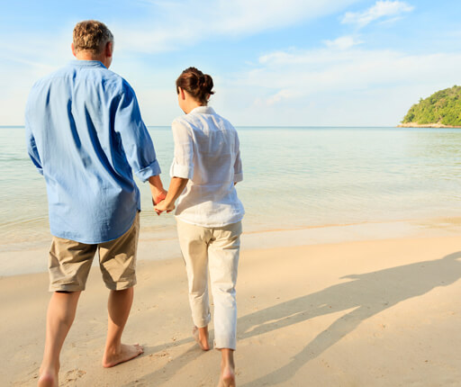 middle age couple walking on beach