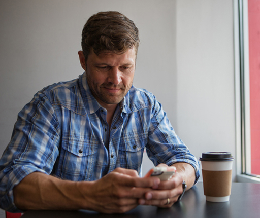 Middle age man using smartphone at coffee shop