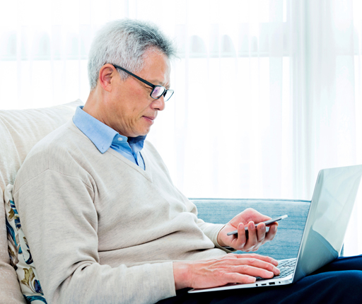 Senior man using laptop and smartphone