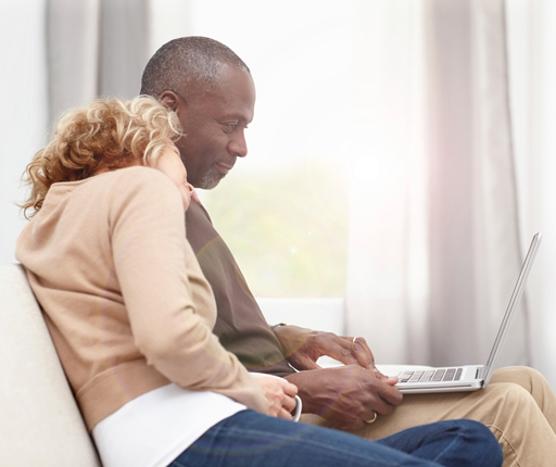 Middle age couple relaxing looking at laptop