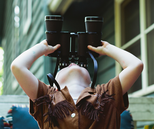 Young boy looking up with binoculars