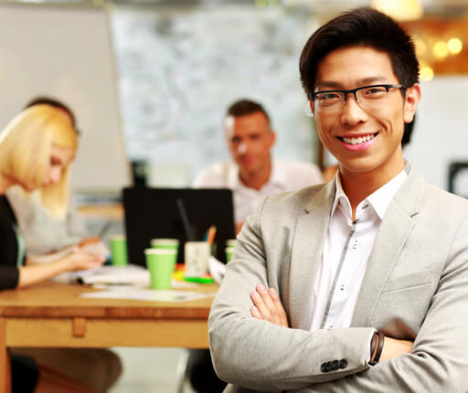 Portrait of cheerful businessman with arms folded sitting in front of colleagues