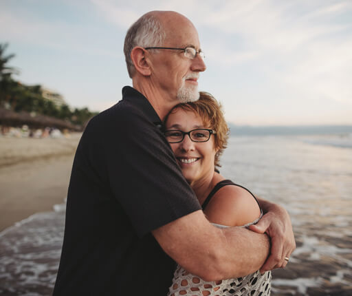 Content middle aged, retired couple hug together outside on ocea